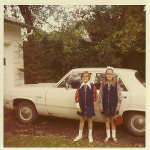 Two girls in front of a 1970 Plymouth Valiant