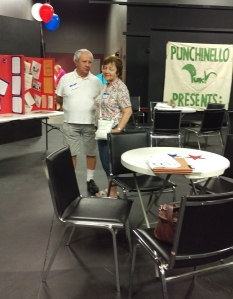 Bob and his wife Audrey, with the drama group banner in back of them and the display boards to their left.