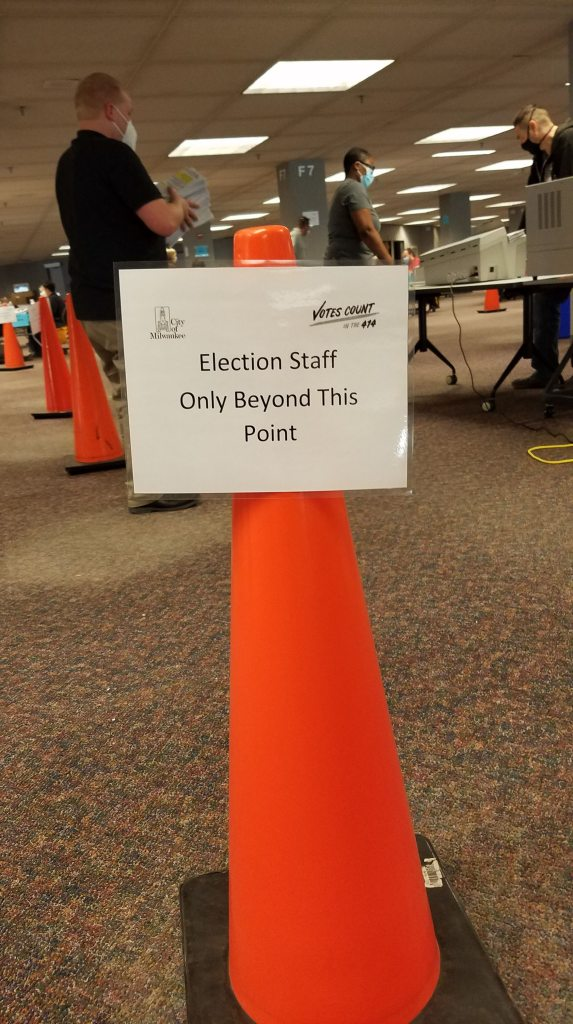 """An orange cone with the sign """"Election staff only beyond this point""""  and election workers lining up to run ballot envelopes through the opener."""