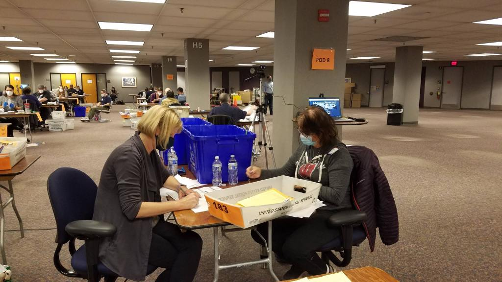Two election workers reconstructing a ballot.