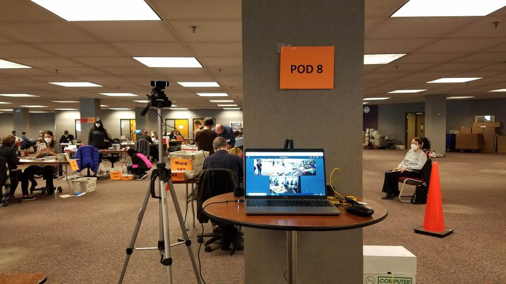 A live-streaming camera setup for the November 3 election and an election observer is seated to the right.
